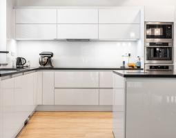 Čistá kuchyně značky Schüller v bílém podání v kombinaci se žulou